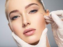 Kobieta dostaje kosmetycznego zastrzyka botox w policzku fotografia royalty free