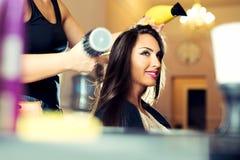 Kobieta dostaje ona włosy suszył przy włosianym salonem obraz stock
