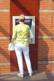 Kobieta dostaje pieniądze od gotówkowej maszyny, Holandia Fotografia Stock