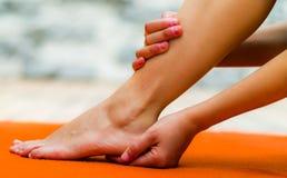 Kobieta dotyka jej czystą stopę, jeden rękę w pięcie i inny w jej nodze, tło pomarańczowy kolor Fotografia Stock