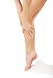 Kobieta dotyka ona nogi zdjęcia royalty free