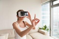 Kobieta dotyka wirtualnych przedmioty w VR słuchawki zdjęcie royalty free