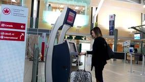 Kobieta druk bagaż etykietka przy Air Canada maszyną - out zbiory