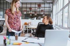 Kobieta dyskutuje pracę z kolegą przy biurem Obraz Royalty Free