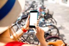 Kobieta dzierżawi bicykl z mądrze telefonem zdjęcie royalty free