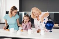 Kobieta, dziewczyna i starsza kobieta, dostajemy przygotowywającymi pić herbaty z kulebiakiem ten one właśnie dostać z piekarnika zdjęcia stock