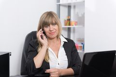 Kobieta dzwoni przy recepcyjnym kontuarem Obrazy Stock