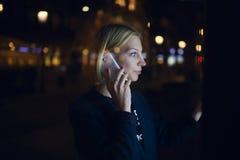 Kobieta dzwoni z komórka telefonem i używa miasto komputer dla turystycznej informaci przy nocą na ulicie podczas gdy stojący Obrazy Stock