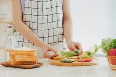 Kobieta fartuch przygotowywa śniadanie w kuchni obrazy royalty free