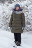 Kobieta folował długość w śniegu, piękną kobiety pozycję w śniegu w zielonej kurtce i trykotowego kapelusz, obrazy royalty free