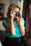 Kobieta fotograf bierze obrazki z retro ekranową kamerą indoors Zdjęcia Royalty Free