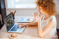 Kobieta fotograf pije kawę i działanie z laptopem na miejscu pracy Zdjęcia Stock