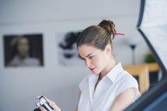 Kobieta fotograf w pracownianej położenie kamerze Obraz Stock