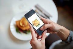 Kobieta fotografuje jedzenie przy kawiarnią z smartphone Fotografia Stock