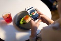 Kobieta fotografuje jedzenie przy kawiarnią z smartphone Zdjęcia Royalty Free