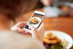 Kobieta fotografuje jedzenie przy kawiarnią z smartphone Zdjęcie Stock