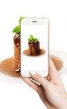 Kobieta fotografuje na smartphone smakowitym torcie Zdjęcie Royalty Free