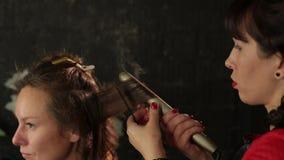 Kobieta fryzjer robi kędziorom przy czerwonym włosy z fryzowań żelazami Piękno bar zbiory