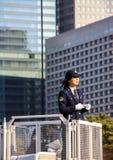 Kobieta funkcjonariusza policji pozycja na wierza i utrzymywać rozkaz Obraz Stock