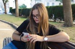 Kobieta gawędzi z smartphone obsiadaniem na ławce w parku z szkłami obrazy royalty free