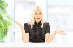 Kobieta gestykuluje niepewność sadzającą w domu Zdjęcia Stock