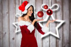 Kobieta gestykuluje przeciw cyfrowo wytwarzającemu tłu w Santa kostiumu Obraz Royalty Free