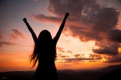 Kobieta gestykuluje sukces - sylwetka nad wieczór niebem zdjęcia royalty free