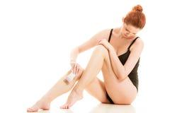 Kobieta goli ona nogi z elektryczną żyletką Obrazy Stock