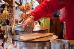 Kobieta gotuje blin przy bożymi narodzeniami wprowadzać na rynek Zdjęcia Royalty Free