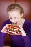Kobieta Gryźć Dużego hamburger Fotografia Royalty Free