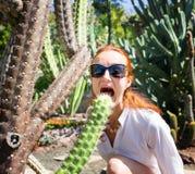 Kobieta gryźć kaktusa w ogródzie Fotografia Royalty Free