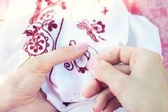 Kobieta Haftuje kwiecistego ornament na pościeli zdjęcie royalty free