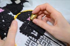 Kobieta haftuje ręcznie broderię na białej tkaninie z czerni i menchii wełny niciami w żółtym obręczu z igłą, obrazy stock