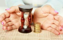 Kobieta hand&-39; s z hourglass i monetą Fotografia Royalty Free