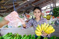 Kobieta handlowiec sprzedaje warzywa, owoc i banany które są dojrzałym kolorem żółtym w wiejskim pobocze sklepie Tajlandia, zdjęcie royalty free