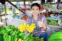 Kobieta handlowiec sprzedaje warzywo banany i owoc które są dojrzałym kolorem żółtym w wiejskim pobocze sklepie w Tajlandia obraz stock