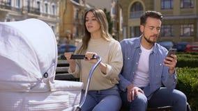 Kobieta huśta się nowonarodzony kareciany patrzeć ze złością przy mężem używa smartphone zdjęcie wideo