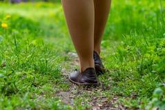 Kobieta iść na piechotę od zadka odprowadzenia wzdłuż ścieżki w lesie z zieloną trawą i kwitnie w lecie zdjęcia stock