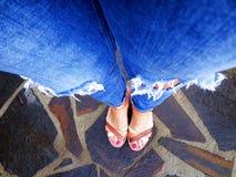 Kobieta iść na piechotę z rozdzierającymi sandałami na kamiennej podłoga i cajgami Zdjęcie Stock