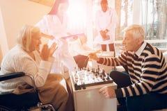 Kobieta i bawić się szachy w karmiącym domu fotografia stock