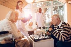 Kobieta i bawić się szachy w karmiącym domu obraz stock