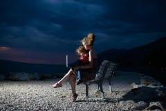 Kobieta i chłopiec z laptopem na plaży obraz stock