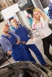 Kobieta i dwa auto mechanika Zdjęcie Stock