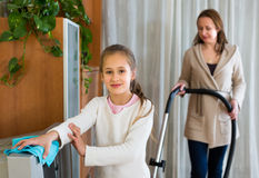 Kobieta i dziewczyna czyści w domu Zdjęcia Stock