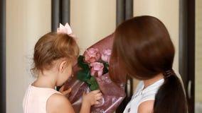Kobieta i jej dziecko dziewczyna z bukietem róże uśmiecha się woń i obwąchuje zbiory wideo