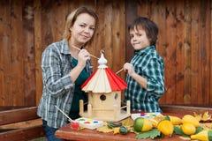 Kobieta i jej syn maluje ptasiego dom Zdjęcia Stock