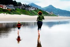 Kobieta i Little Boy bieg na plaży z odbiciem w Mokrym piasku obraz stock