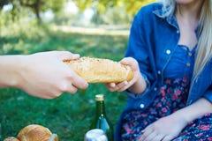 Kobieta i mężczyzna drzeje chleb na pinkinie Zdjęcia Royalty Free