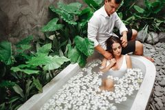 Kobieta i mężczyzna relaksuje w skąpaniu z tropikalnymi kwiatami plenerowymi przy luksusowego hotelu kurortem obrazy royalty free