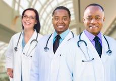 Kobieta i Męskie lekarki w Hospit Kaukaskie i amerykanin afrykańskiego pochodzenia Zdjęcie Royalty Free